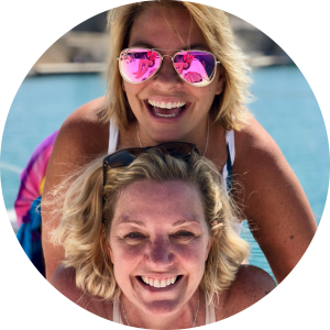 Kelli Carpenter and Anne Steele on vacation together, wearing sunglasses and smiling at the camera